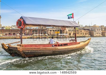 Dubai, United Arab Emirates - May 3, 2013: Abra ferry along Dubai Creek. The Creek divides the city in Deira and Bur Dubai. Abra is a traditional mode of transport between Deira and Bur Dubai.
