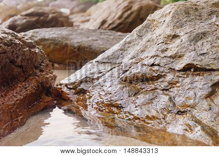 Close up of rocky shore texture background. Stones Rocks Sand on sunset time. Selective focus