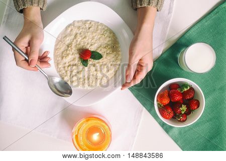 Oatmeal with milk. Porridge with milk. Cereals, delicious Breakfast, diet Breakfast. Strawberries, oatmeal and glass of milk. Hands of a young woman with a spoon. healthy eating cocept, selective focus.