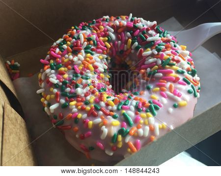 A delicious donut with strawberry icing and rainbow sprinkles.
