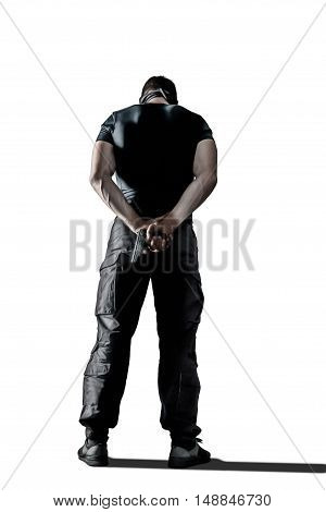 Standing man with gun wearing black military uniform isolated on white background, behind view