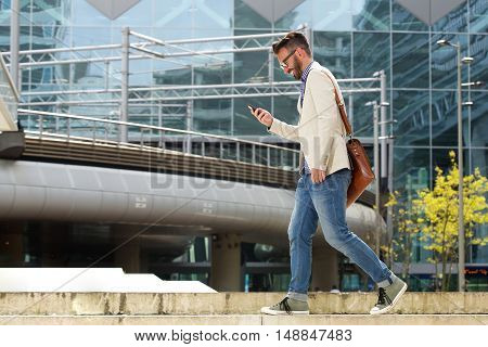 Happy Caucasian Man Walking Outdoors And Reading Text Message