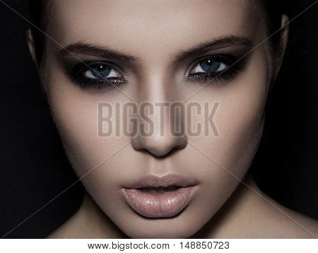 Beautiful woman model smokey eyes makeup close up on black background