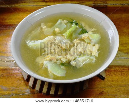 boiled egg with cabbage in hot soup on bowl