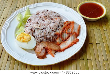 barbecued red pork in sweet sauce with brown rice on dish