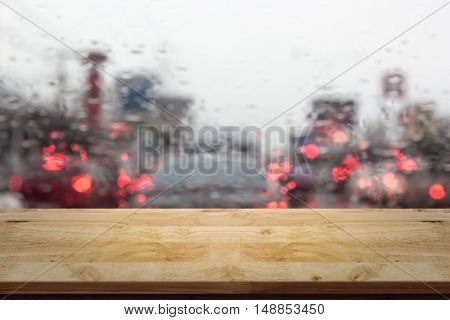 View through glass with empty top wood table and abstract blur rain and driving background.