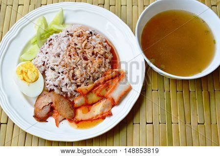barbecued red pork in sweet sauce with brown rice and soup