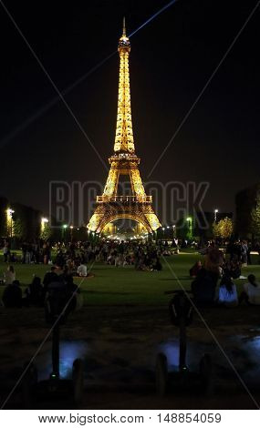 PARIS, FRANCE - SEP 09, 2014: Many tourists near the illuminated Eiffel tower on the Champ de Mars in the evening