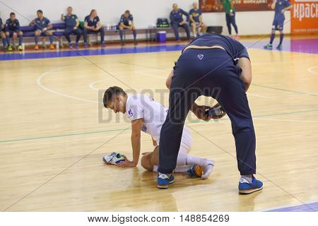 MYTISHCHI, RUSSIA - OCT 16, 2014: Football player sprained his ankle during the game on the Russian Futsal Super League in the Sports Complex Construction in Mytishchi