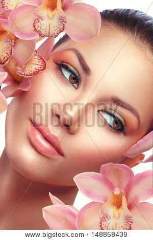 Beauty Young Woman Face, Skin care, Spa. Beautiful brunette model girl portrait with orchid flowers, perfect makeup, fresh skin. Isolated on white background. Plastic surgery, fillers injections