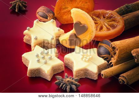 Star Christmas cookies and spices on red background as a Xmas background
