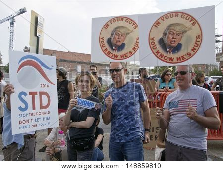 Asheville,North Carolina, USA: September 12, 2016: Protesters hold signs at a Donald Trump Rally saying not tolet him infect our country and in your guts you know he's nuts on September 12, 2016 in downtown Asheville, NC