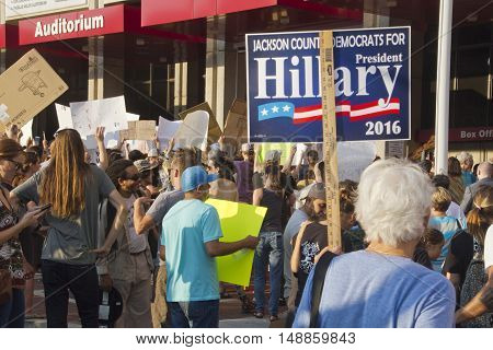 Asheville, North Carolina, USA: September 12, 2016: Senior Woman holds a Hillary Clinton sign among a crowd of protesters at a Donald Trump campaign rally on September 12, 2016 in downtown Asheville, NC