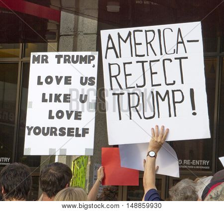 Asheville, North Carolina, USA: September 12, 2016: Protesters at a Donald Trump campaign rally hold signs saying that