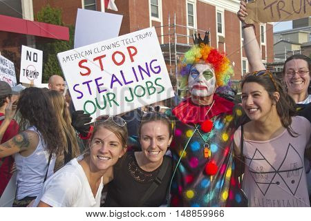Asheville, North Carolina, USA: September 12, 2016: Donald Trump rally protesters including a colorful clown holding a humorous sign saying