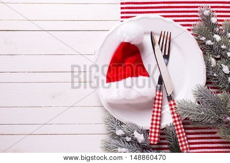 Christmas table setting. White plate knife and fork napkin and christmas decorations in white and red colors on white wooden table. Top view. Place for text. Selective focus.