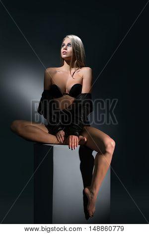 Erotica. Leggy girl posing sitting on cube in studio