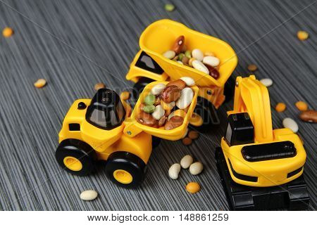 Three yellow toy truck on a grey stone background with beans selective focus