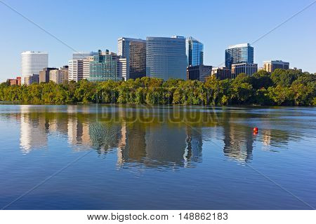 Rosslyn skyscrapers in the early morning with reflections in Potomac River. Beautiful morning at Georgetown Park with Virginia suburb across the river.