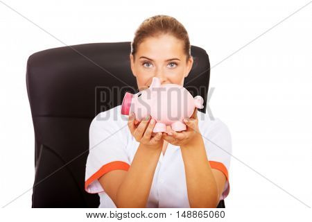 Smile doctor sitting behind the desk and holding a piggybank