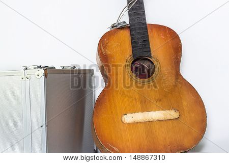 Broken brown classical guitar with detached bridge from body isolated in white background. White metal box