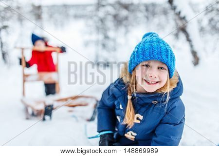 Adorable little girl and cute boy outdoors on Christmas day having fun sledding in snow