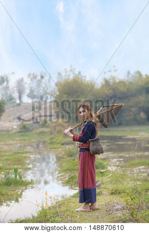 Asian beautiful lady in tribe dress stand near swamp with fishing gear in hand.Thailand