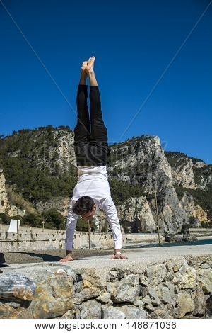 Young strong man in pants and shirt in handstand against of rocky mountains and bright blue sky in sunlight