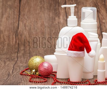Christmas skincare cosmetics. Various cosmetic products for face and body care with Santa hat on wooden surface. Copy space. Christmas sale or gift concept, focus on hat