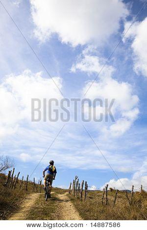 Young man riding mountain bike and watching cloudy sky