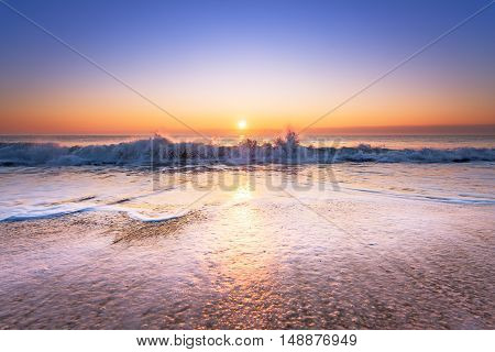Wave on the beach at sunset. Golden sands.