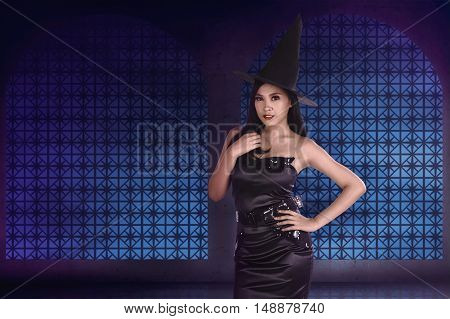 Portrait Of A Gorgeous Asian Witch In Black Dress And A Hat