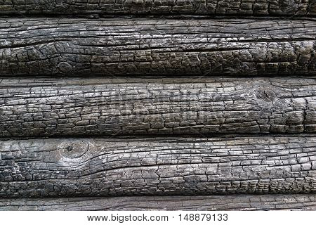 Charred wall of the house of pine trees logs. Burnt wall of the house. Conceptual background charred walls of the timber. Burnt pattern. Burnt wooden house wall. Black burned wooden house texture.