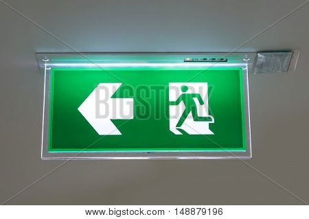 green emergency exit sign showing the way to escape poster