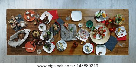 After banquet is finished. Wasted food on wooden served festive table after dinner party. Leftovers, empty plates, left half eaten food and meals. Top view