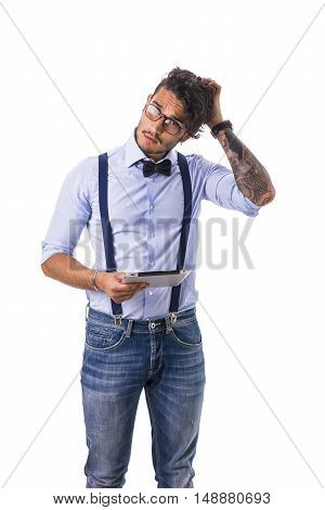 Portrait of brunette young man in light blue shirt, suspenders and jeans, using tablet PC, standing in studio shot isolated against white background.