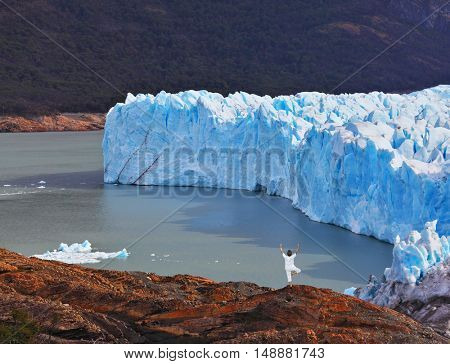 Giant lake glacier of Perito Moreno. The woman ashore in a white suit for yoga carries out a pose