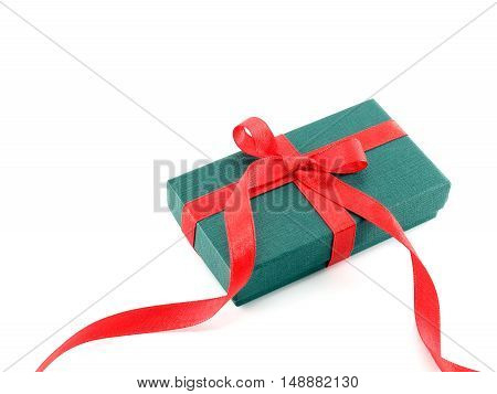 close up small green gift box with long red ribbon bow isolated on white background