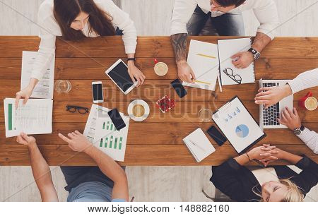 Business meeting. Young people work in office, top view of wooden table with mobile phones, laptop, tablet and documents papers with diagram. Men and women team together have brainstorm discussion.