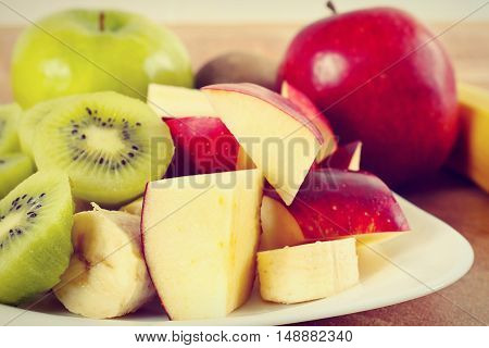 Fresh whole and sliced apple and kiwi close up gently toned