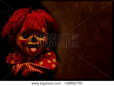 Grunge Halloween background with old stucco wall texture of brown color and spooky clown