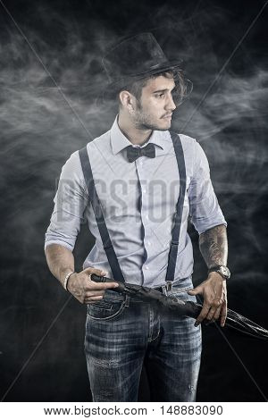 Portrait of brunette young man in glasses, hat, bow-tie, suspenders and shirt on dark smoky background. Vintage look