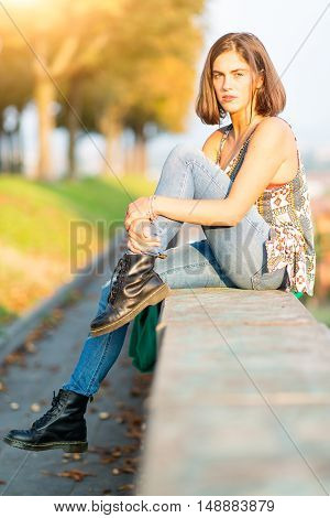 Young Beautiful Girl Sitting On A Low Wall In A Park In The City