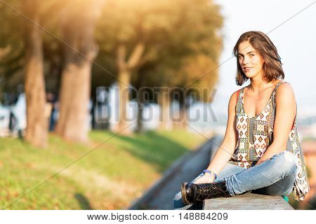 Young beautiful girl sitting on a low wall in a park in the city in the sun