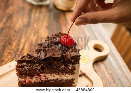 Woman hand pick up the cherries topping from slice of chocolate cake on wood table.