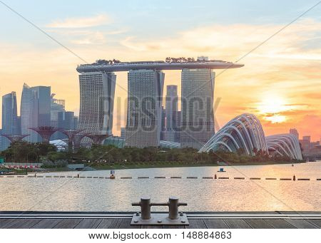 Singapore, Republic of Singapore - May 4, 2016: Supertree grove, Cloud garden greenhouse and Marina Bay Sands hotel reflecting in water at sunset