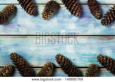 Winter, christmas background. Natural and painted in gold fir cones on a blue background vintage. With the overlay bokeh effect