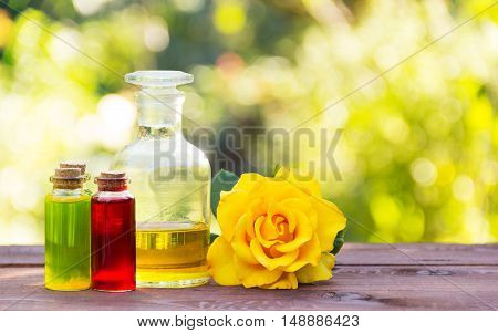 Natural rose oil and flower elixirs body. Spa treatment and massage. Fragrant yellow rose. Vintage glass bottles. Aromatherapy and Alternative Medicine. Green blur. Copy space. Spa concept.