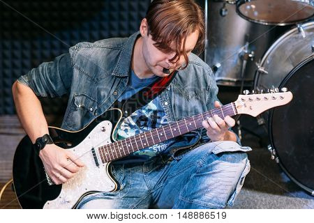 Bass guitar player playing solo, close-up. Young male guitarist play music during alive performance.
