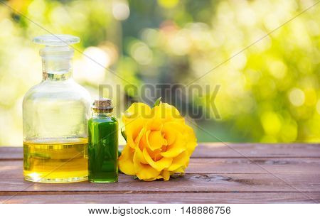 Natural rose oil and flower green elixirs body. Spa treatment and massage. Fragrant yellow rose. Vintage glass bottles. Aromatherapy and Alternative Medicine. Green blur. Copy space. Spa concept.